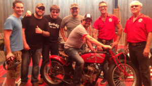 Seven smiling men from young to older, one holding a video camera, one sitting on an Indian motorcycle and all posing for the camera. Five of the younger men are wearing t-shirts. The two older men are wearing red company short-sleeved shirts.